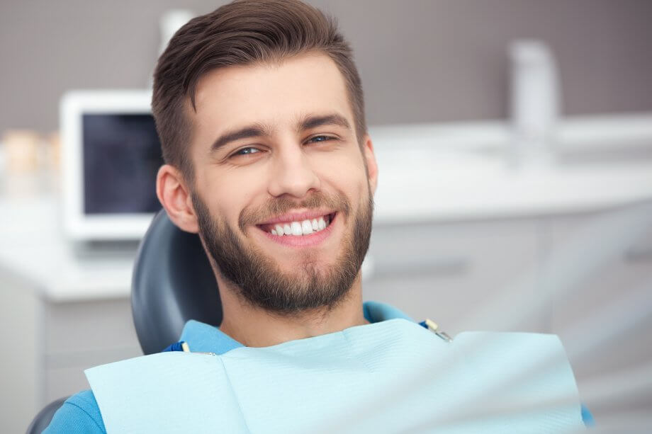 Photograph of a man with short brown hair and a beard smiling while sitting in a dentist chair.