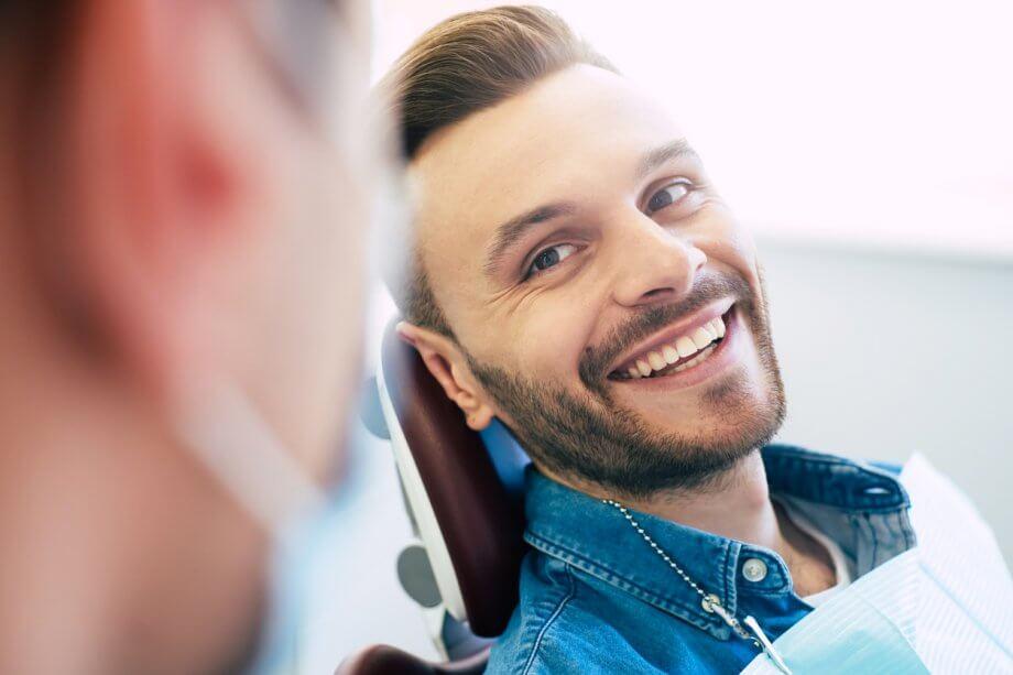 Man in Dental Chair Smiling After Dental Implants